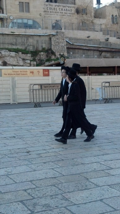 A group of three Hasidic Jews walk at the Western Wall in Jerusalem.