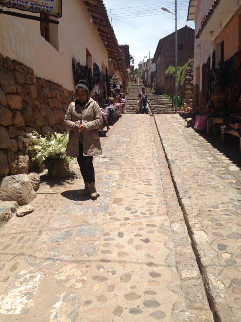 Walking up a steep hill in a village outside Saksaywaman.