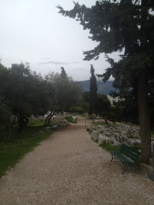 A walkway leading through the ruins at the Acropolis. Athens can be seen through the trees.