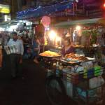 Thai woman at outdoor food stand at night on a busy sidewalk area.