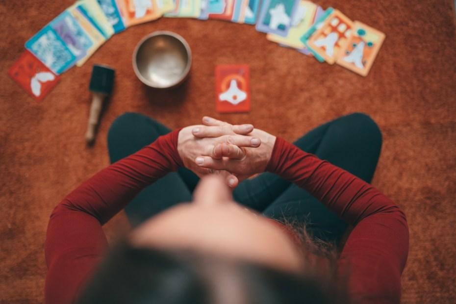 Mujer sentada meditando con un tazón tibetano y cartas de oráculo.