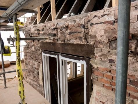 Facade stone removed reveals irregular inner brick wall