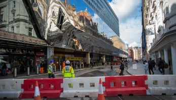 Stephenson Street is almost clear apart from two temporary traffic blocking barriers. Note the super large distorted mirror effect the stainless steel cladding presents to the visitor.