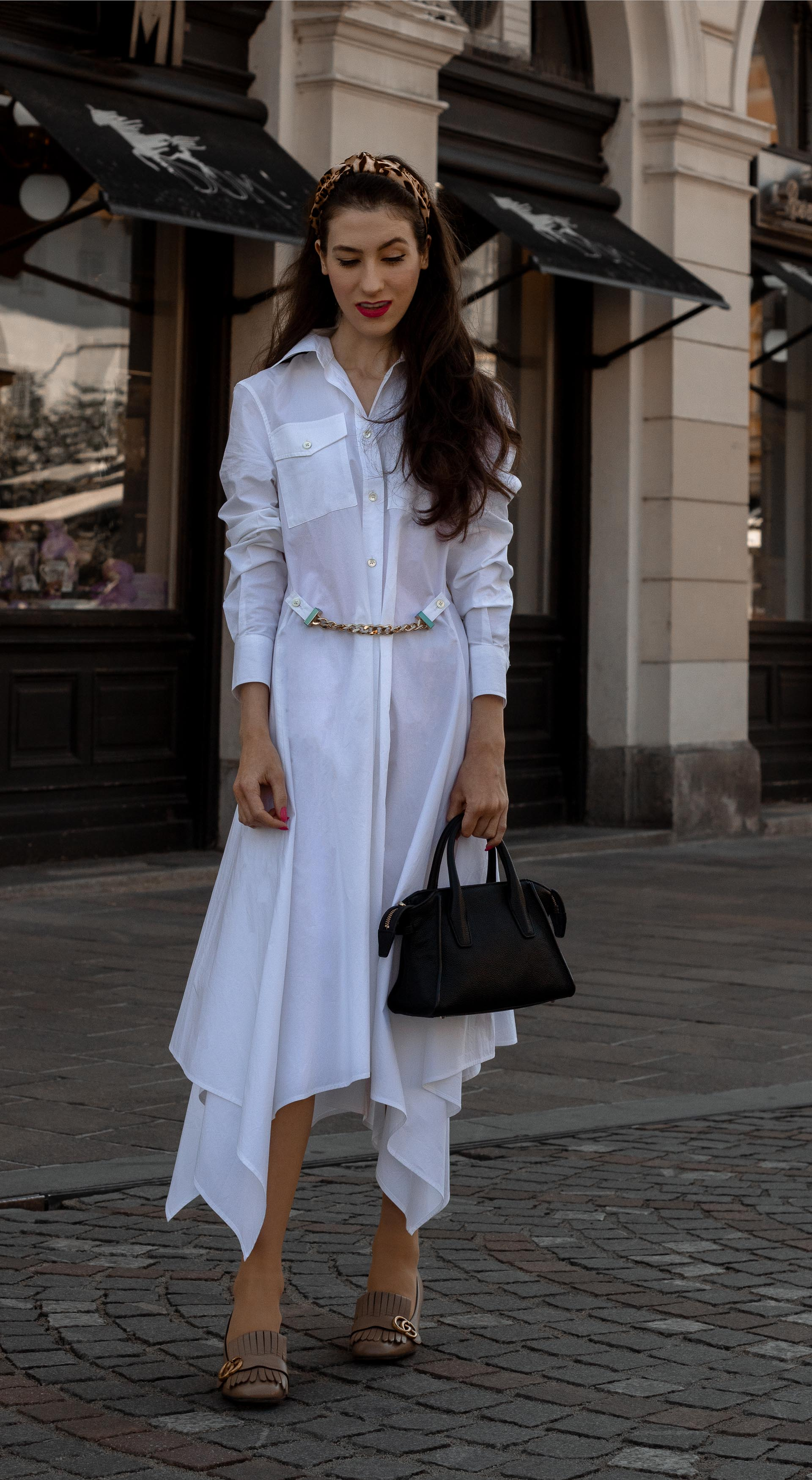 Fashion blogger Veronika Lipar of Brunette from Wall Street dressed in white JW Anderson chain belt shirt dress Gucci heeled loafers Jennifer Behr leopard print headband for work in fall