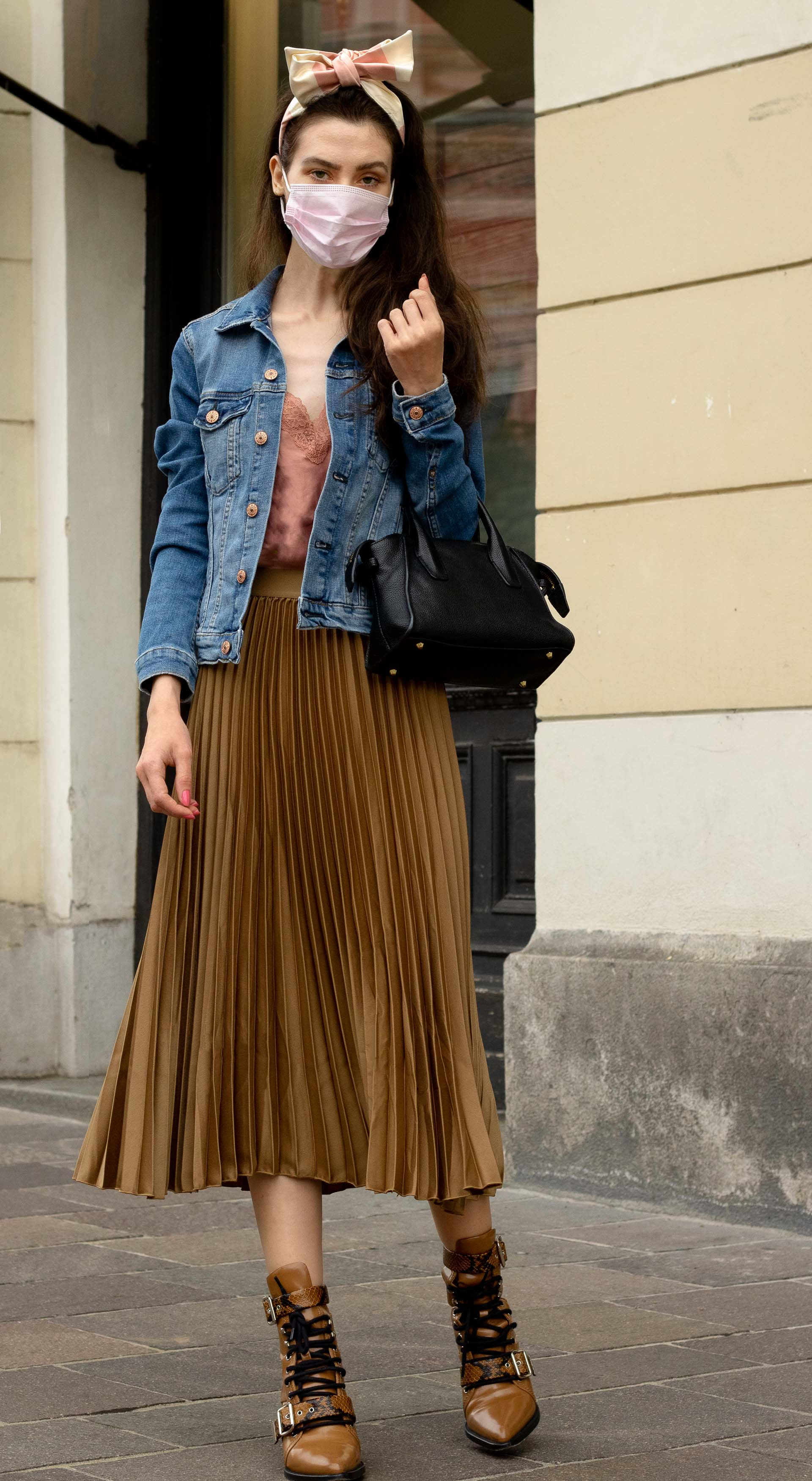 Fashion blogger Veronika Lipar of Brunette from Wall Street dressed in casual summer to fall outfit H&M denim jacket Etam slip top H&M gold pleated midi skirt Chloé Rylee boots bow headband pink face mask on the street in September