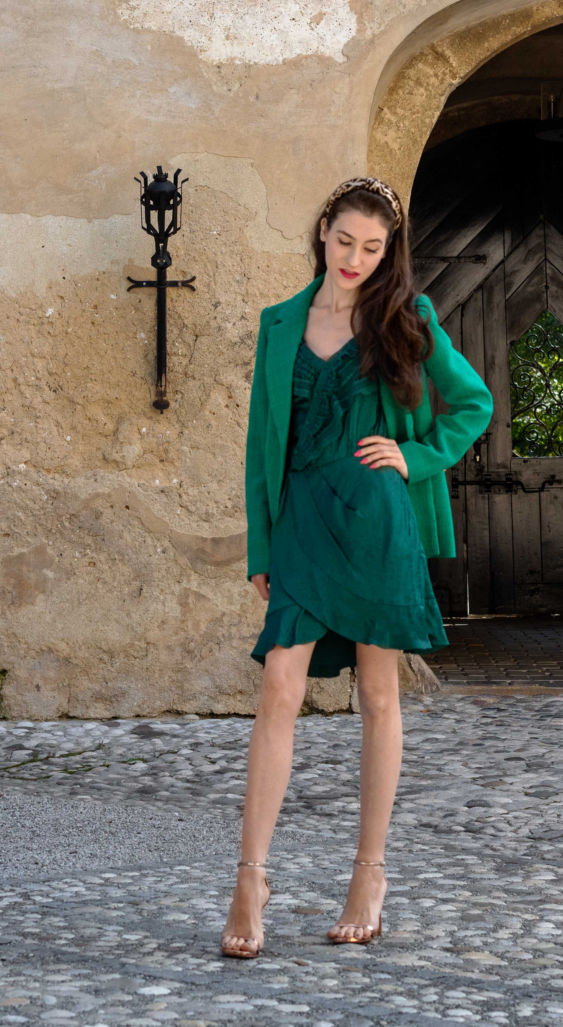 Fashion blogger Veronika Lipar of Brunette from Wall Street dressed in sexy formal wedding guest outfit green one shoulder self-portrait dress Sandro Paris double breasted blazer Stuart Weitzman sandals for micro garden wedding in late summer