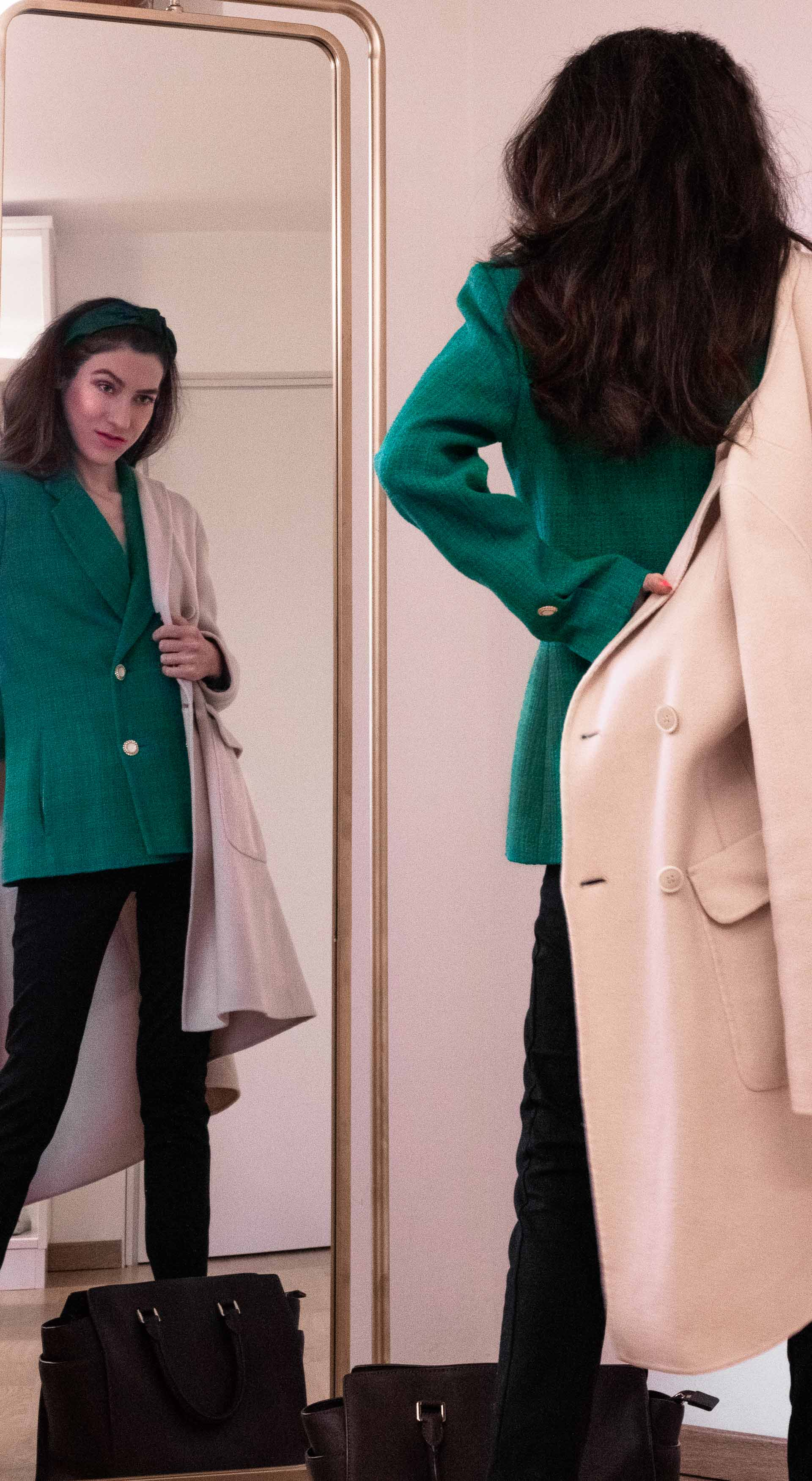 Fashion blogger Veronika Lipar of Brunette from Wall Street wearing Sandro Paris green blazer black leggings putting on a coat in front of the mirror before going to work