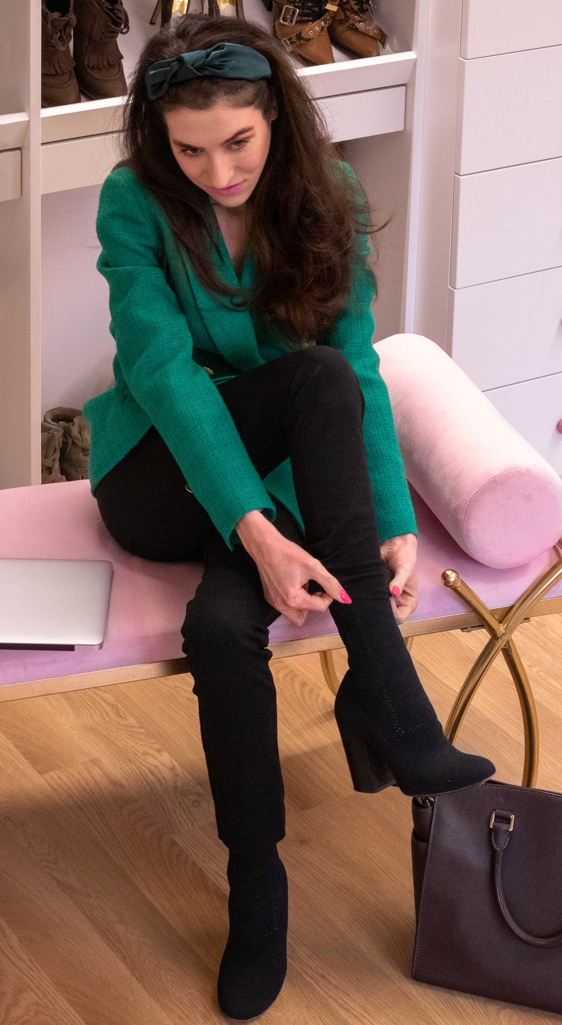 Fashion blogger Veronika Lipar of Brunette from Wall Street wearing Sandro Paris green blazer black leggings sitting on the bench putting on black sock boots in dressing room