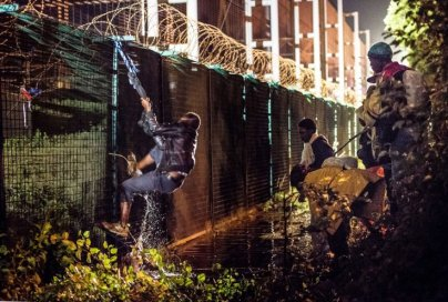 migrant-climbs-security