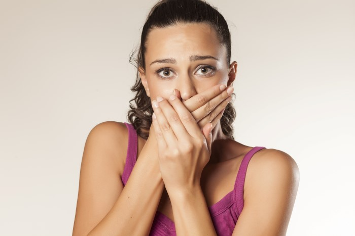 embarrassed young brunette covering her mouth with both hands
