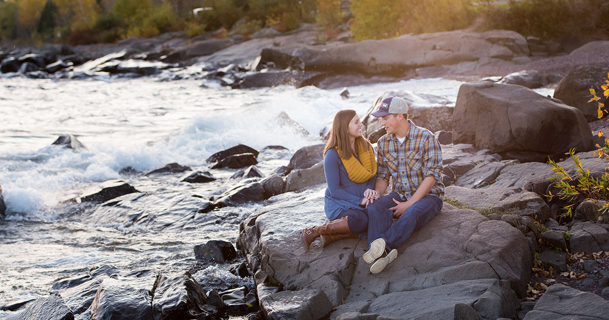 Engagement couple photo sitting beside running water in fall.