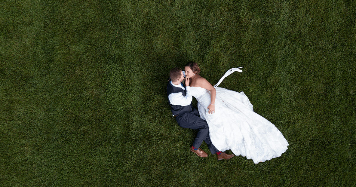 Bride and groom lying down, photo taken from above.