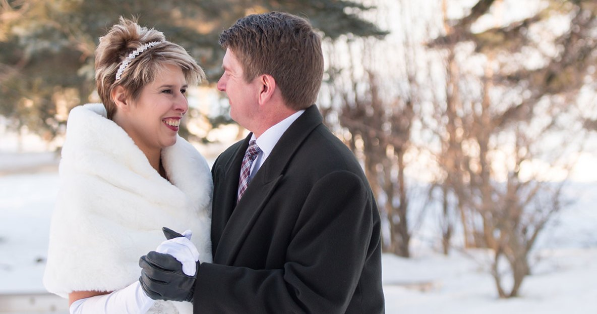 Bride and groom portrait outside with snow in background.