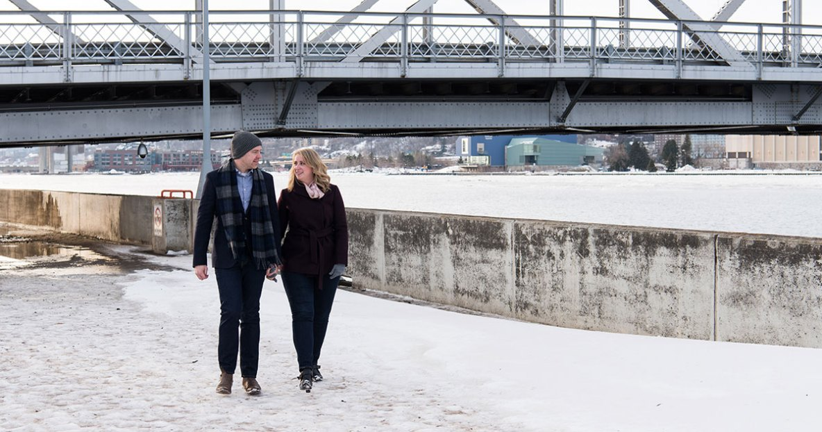 Winter engagement session with snow and lift bridge in background.