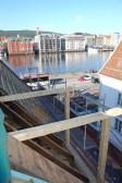 Vindearken vert montert i godt ver. Det er fin utsikt til eit speilblankt havnebasseng. På biletet er stolpane reist med nederste sperreramme påmontert.