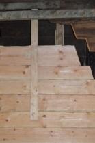 Undersiden er ferdig tilpasset. Neste steg er å tilpasse oversiden mot det gamle laftet. For å ha kontroll på stokkens plassering sidelengs skrur vi på et loddbord og en kloss