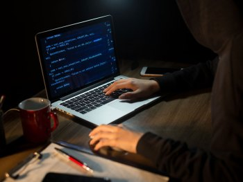 Hacker sitting at desk with a laptop