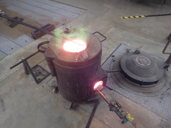 Melting the bronze in the furnace.