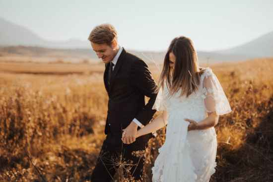 shallow focus photo of man in black formal suit holding woman s hand in white dress