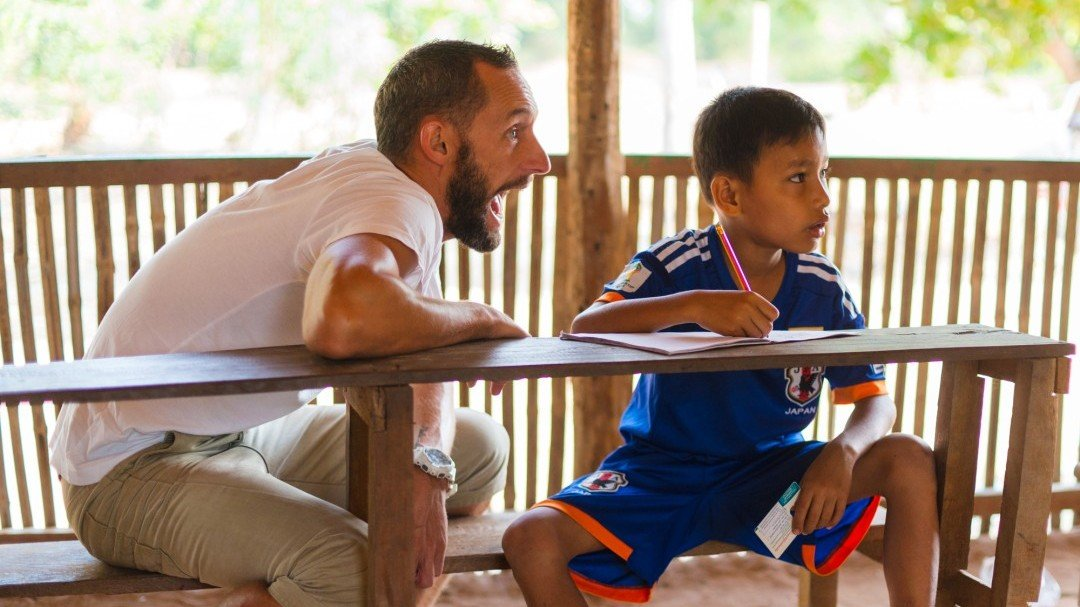 a volunteer teacher interacts with a student at the CESHEO Svay Thom campus near Siem Reap, Cambodia