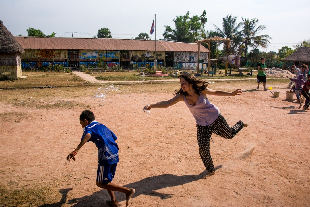 Students and teachers participate in a water fight at the CESHEO Svay Thom campus near Siem Reap, Cambodia