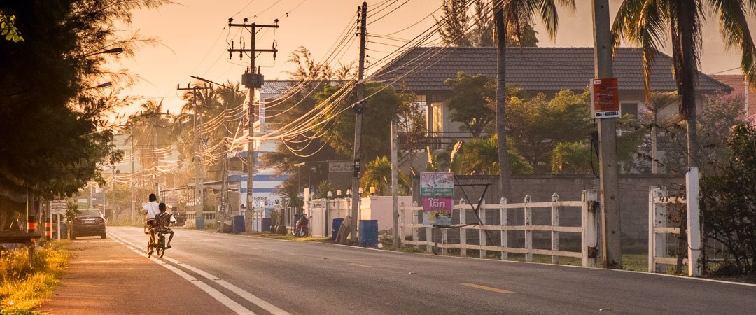 2 friends ride a bike down the road on Sam Roi Yot Beach, Thailand