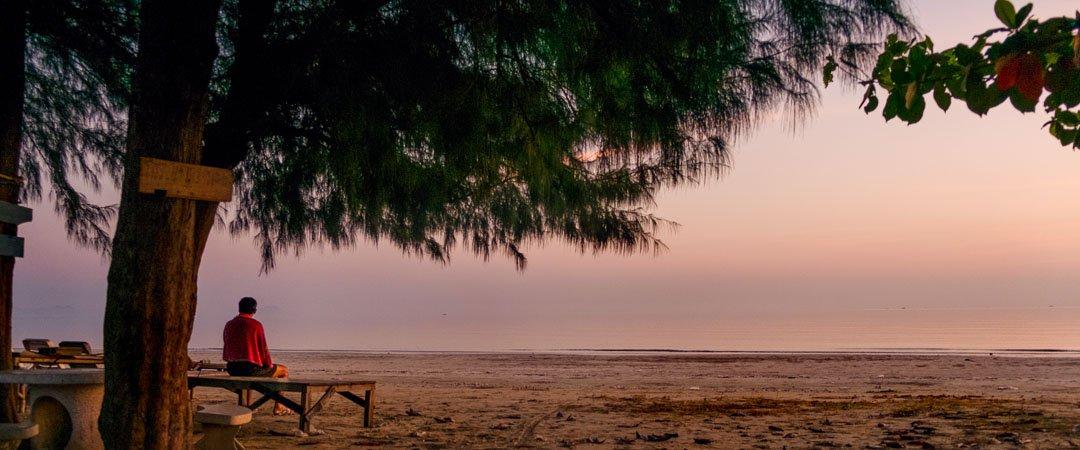 a man meditates under a tree on Sam Roi Yot Beach in Thailand