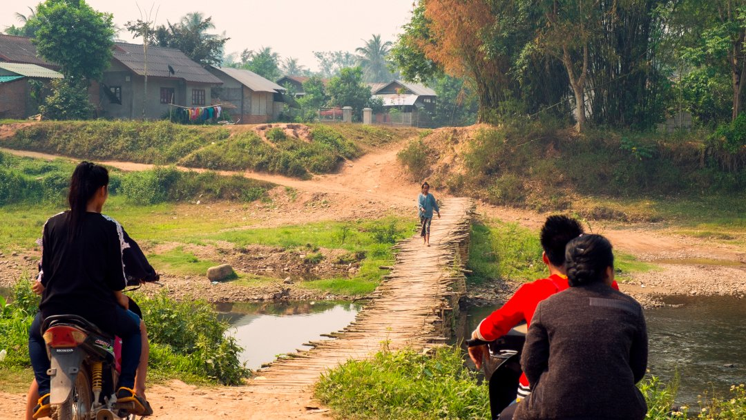 Photo of people on motorcycles waiting to cross a bamboo bridge in Luang Namtha, Laos