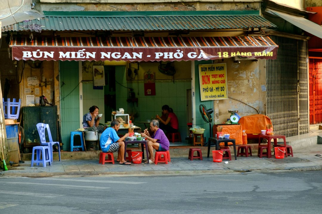 Diners eating breakfast at a street corner cafe - Old French Quarter, Hanoi, Vietnam