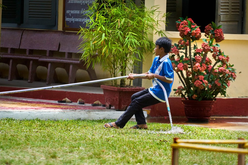 Photo of a boy pulling on a hose by humanitarian photographer Bryon Lippincott