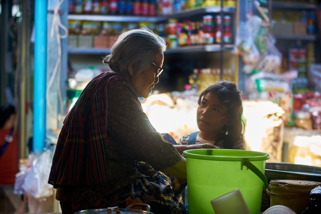 Photo of a grandmother and granddaughter talking in a market by humanitarian photographer Bryon Lippincott
