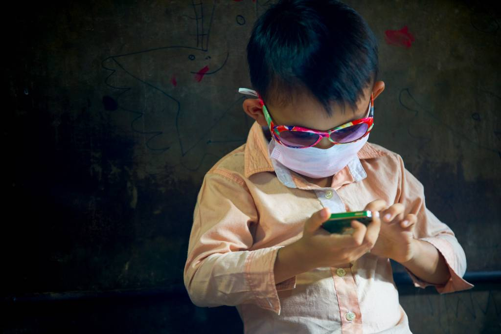 Photo of a boy playing with an iphone by humanitarian photographer, Bryon Lippincott