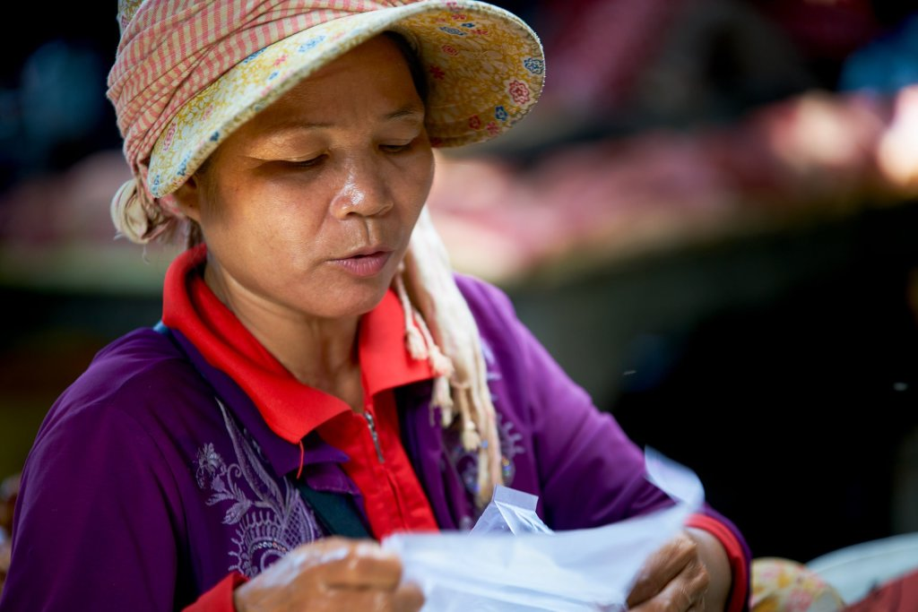 Photo of a woman working in a market by Humanitarian Photographer Bryon Lippincott