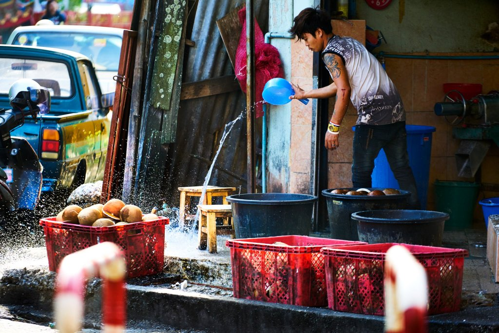 Photo of A man cleaning up in Warorot Market in Chiang Mai, Thailand by humanitarian Photographer Bryon Lippincott