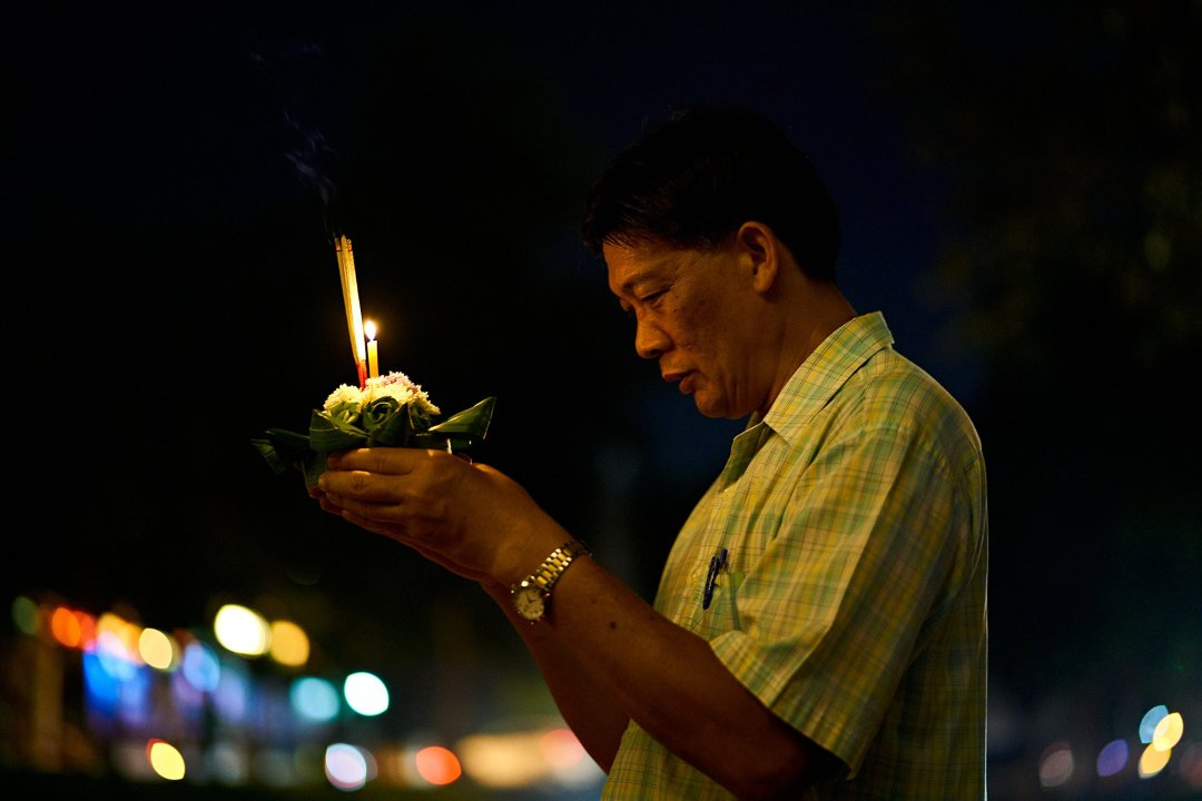 Photo of a man offering a prayer before launching his Krathong  in Chiang Mai, Thailand during the Loi Krathong Festival on November 11, 2019 by Bryon Lippincott