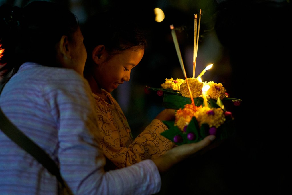 Photo of a mother and daughter making wishes as they prepare to launch their Krathong during the Loi Krathong festival in Chiang Mai, Thailand on November 11, 2019 by Bryon Lippincott