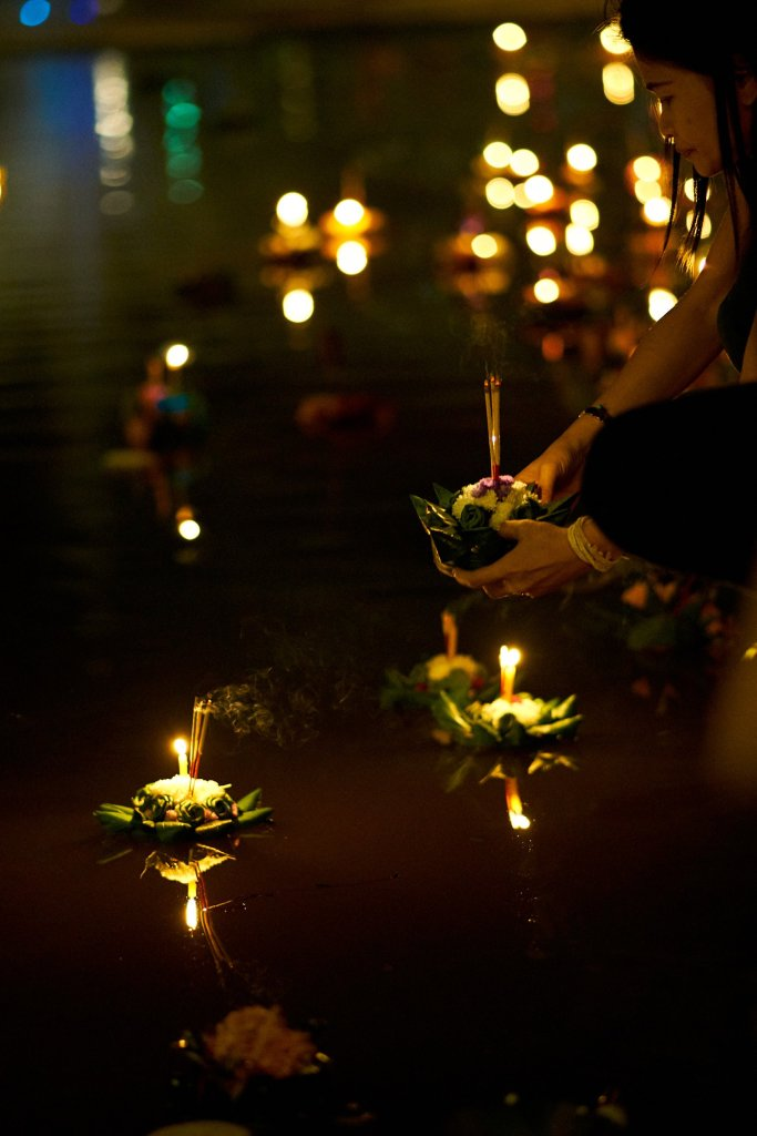 Photo of woman preparing to launch her Krathong into the moat in Chiang Mai, Thailand during the Loi Krathong festival on November 11, 2019 by photographer Bryon Lippincott