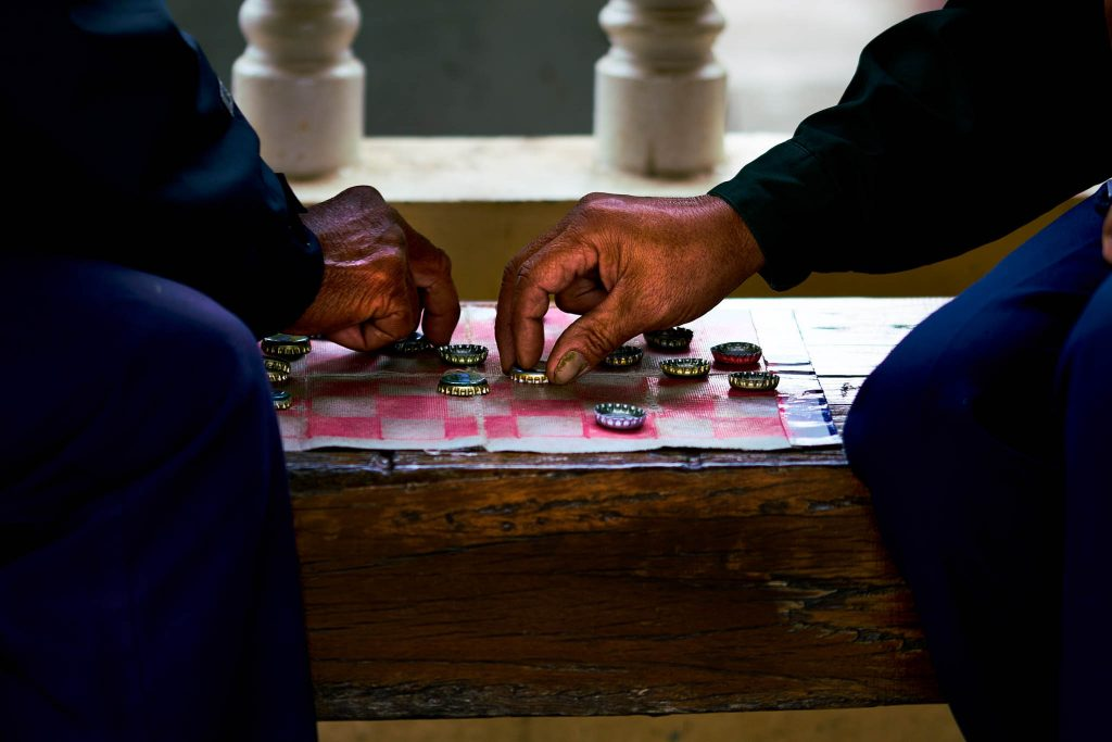 photo of 2 men playing chess in a train station in Northeast Thailand by Bryon Lippincott
