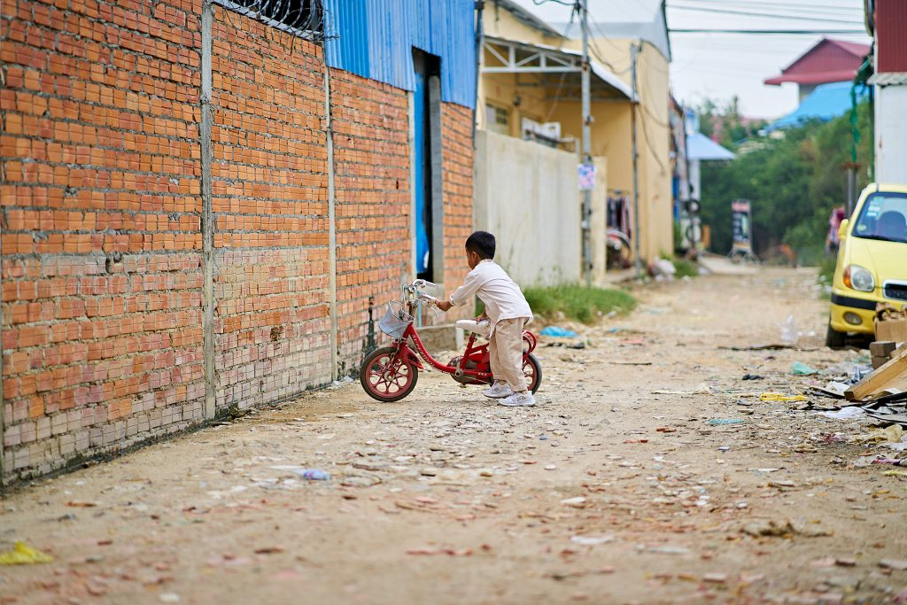 Photo of a boy riding his bike in Phnom Penh, Cambodia by Humanitarian Photographer Bryon Lippincott