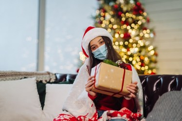 Girl holding a Christmas present on New Years Eve. Girl looking at the camera. Christmas during coronavirus, concept