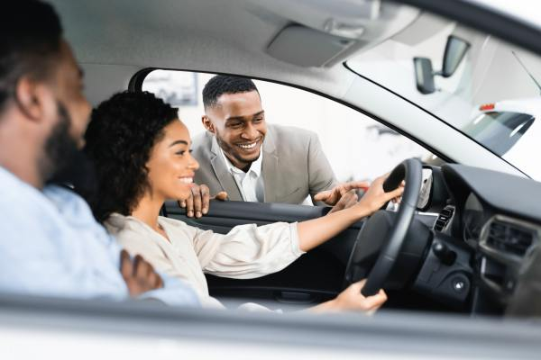 Couple Buying Car Testing It With Dealer Sitting In Auto