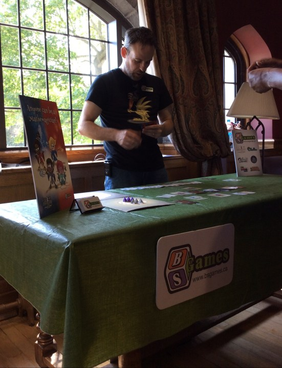 Bill looks at his Mathemagician's Duel cards behind our table.
