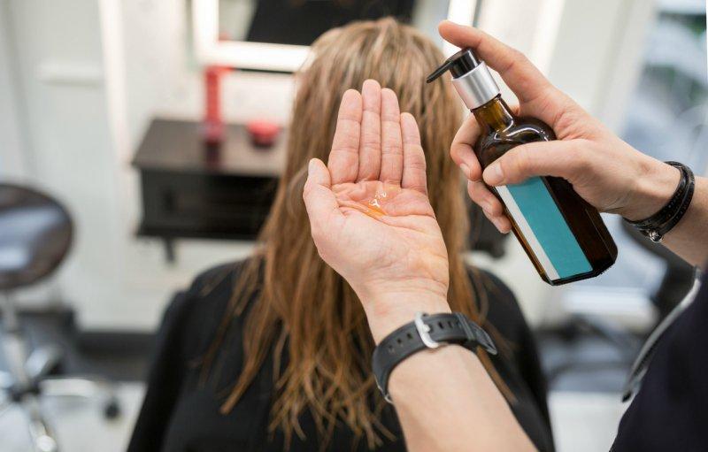 PhotosHairdresser squeezing hair conditioner on hand