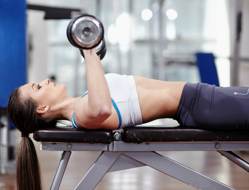 Young woman bench pressing with dumbbells in the gym working triceps and chest