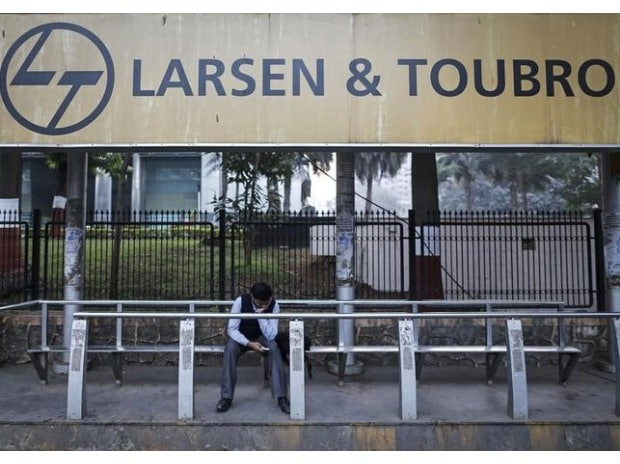 A man waits at a bus-stop with an advertisement of Larsen & Toubro outside the company's manufacturing unit in Mumbai