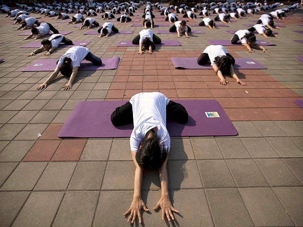 Participants strike a pose during a group yoga session at a park in Beijing. Several hundred Chinese yoga enthusiasts participated in a mass yoga session to mark International Yoga Day, which falls on June 21. Photo: PTI