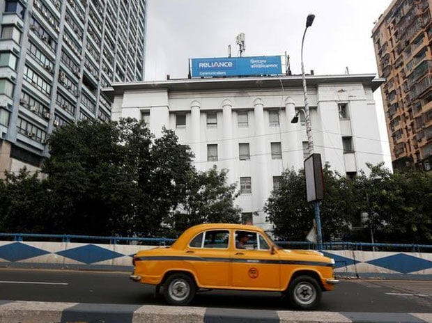 A taxi drives past a Reliance Communications office building in Kolkata. Photo: Reuters