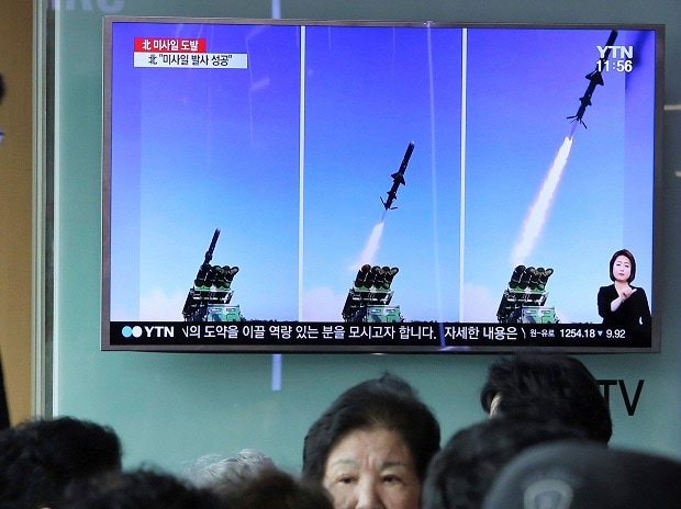 A man watches a TV news program showing photos published in North Korea's Rodong Sinmun newspaper of North Korea's new type of cruise missile launch, at Seoul Railway station in Seoul, South Korea June 9.