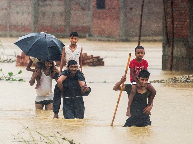 Birgunj :  Nepalese men carry children on their shoulders as they wade through flood waters in village Ramgadhwa in Birgunj, Nepal, Sunday, Aug. 13, 2017. An official said torrential rain, landslides and flooding have killed dozens of people in Nepal