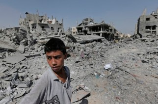 A Palestinian stands in the rubble of destroyed houses Aug. 1 in the heavily bombed town of Beit Hanoun, Gaza Strip, close to the Israeli border. AP/Lefteris Pitarakis